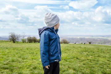 young boy is looking at blue sky