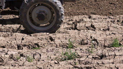 Closeup on tractor working in the field with a power harrow