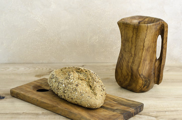 Organic bread over olive wooden cutting board and pitcher.