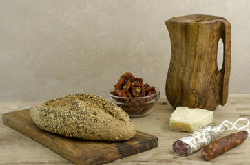 Bread, olive wooden cutting board and pitcher.