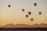 Sky lanterns flying upwards.