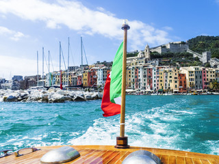 Cinque Terre glimpse in Liguria from watercraft and italian flag