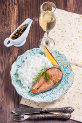 Baked salmon with rice garnish and a glass of white wine