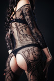 Sexy beautiful naked woman in black erotic lingerie on dark