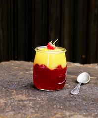 Mango and raspberry dessert in a glass jar