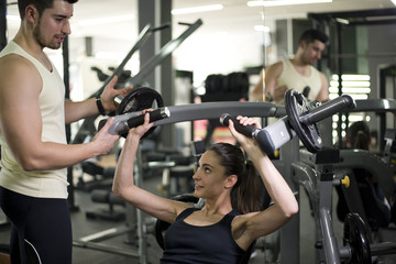 Gym coach helping girl doing pectoral exercises