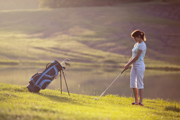 Young female playing golf near the lake.