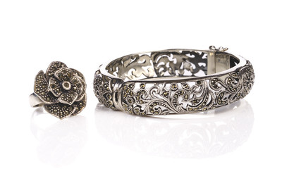 Silver bracelet and ring on white a background