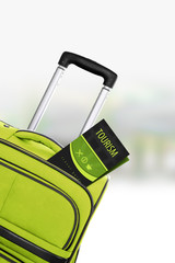 Tourism. Green suitcase with guidebook.