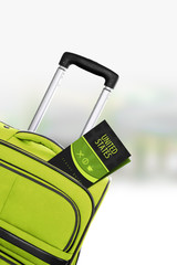 United States. Green suitcase with guidebook.
