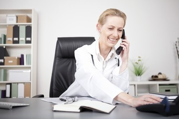 Happy Physician Leaning on Table While on Phone