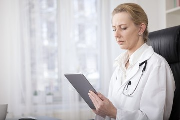 Serious Woman Doctor Holding a Tablet Computer