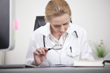 Female Doctor Reading Using Magnifying Glass