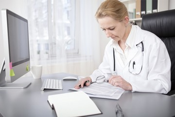 Woman Doctor Writing and Reading at her Office