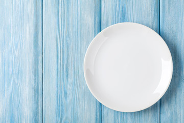 Empty plate on blue wooden background