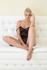 Sexy blonde dressed in negligee posing on sofa