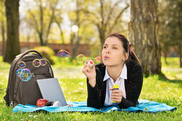 Young girl lying on a meadow blowing soap bubbles