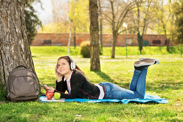 Young girl listening music in the park