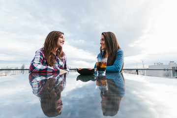 Two Friends Having a Drink in a Bar Terrace with Views