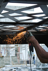 Construction workers using grinder to cut steel