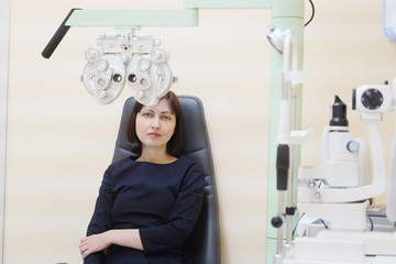 Portrait of a woman sitting behind the phoropter during eye exam