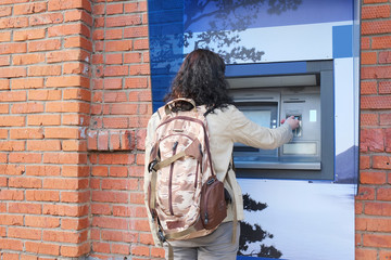 Woman with backpack withdrawing money from credit card at ATM.