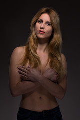 Topless woman covering breast