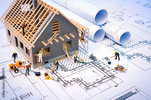 building house on blueprints with worker - construction project - 81895775