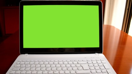 hands with a calculator in front of a laptop with chroma