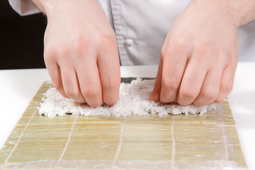Chef puts rice on a bamboo mat