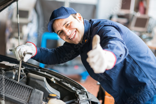 Auto mechanic working on a car in his garage - 81896793