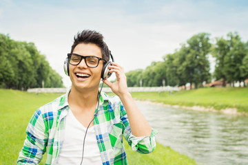Young hipster man with headphones outdoors