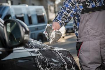 Handwäsche am Auto mit Schwamm und Schaum auf der Straße