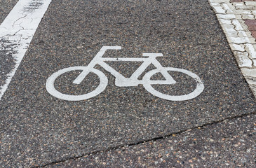 White bicycle lane sign on the tarmac street