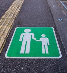 The pedestrian walking lane sign on the tarmac footpath