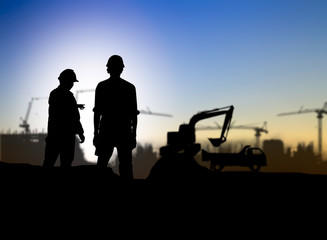 silhouette engineer looking Loaders and trucks in a building sit