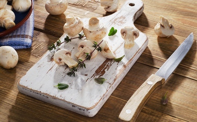 Fresh white mushrooms  on  wooden cutting board.