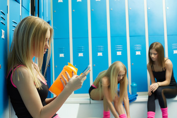 Before training. Sexy girls resting in locker room