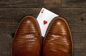 Poker player with card under cowboy boot..