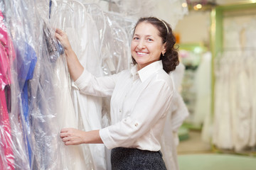 woman  chooses gown at boutique