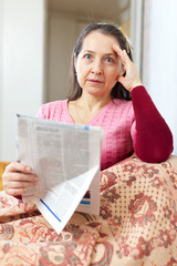 affliction mature woman with newspaper