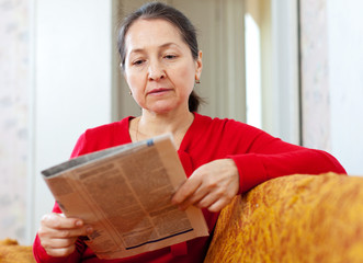 serious  woman looks newspaper