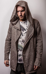 Studio portrait of young handsome man in casual cape with a hood