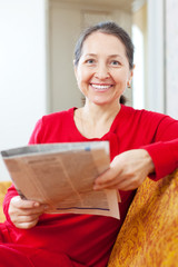 cheerful positive mature woman reads newspaper
