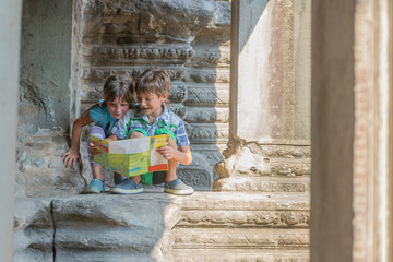 two young children looking at tourist map in Angkor wat, cambodi