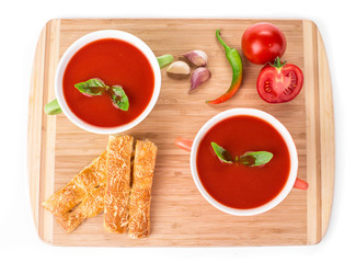 Bowl of tomato soup on wood platter.