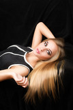 Charming young woman with beautiful blonde hair lying. poster