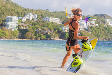 A young woman kite-surfer ready for kite surfing rides in blue s