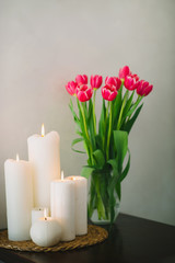 Bouquet of pink tulips with beautiful candles