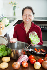 mature woman cooking soup with rice